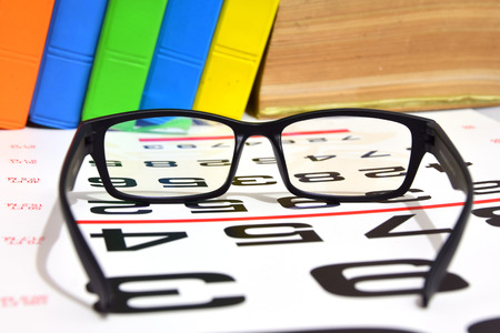 bifocals: Reading book glasses with eye chart  (shallow DOF) Stock Photo