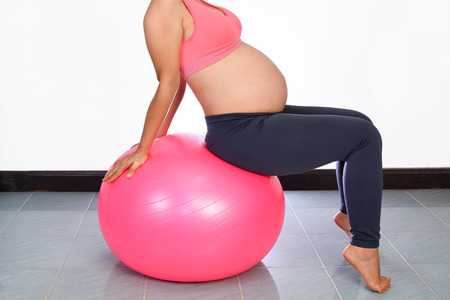 Pregnant woman yoga with exercise gymnastic ball
