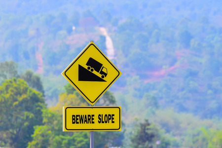 beware: Beware slope Sign, with blurred uphill road.