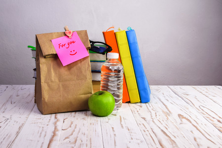 to lunch: bolsa de papel almuerzo con manzana, el agua y los libros en el escritorio con la nota, Foto de archivo