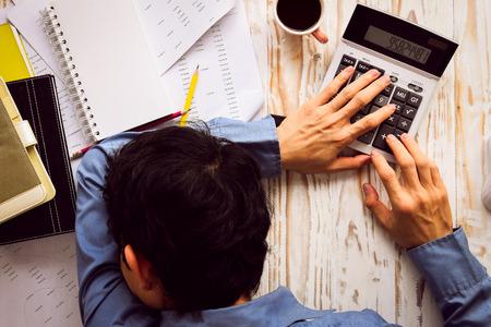금융 시트 계산기와 커피와 함께 사무실 책상에서 자고 사업가입니다. (과로에 대한 개념)