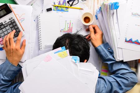 calculadora: Empresario pesada carga de trabajo del sue�o en el escritorio de la oficina con la calculadora hoja de finanzas y caf�. (Concepto de exceso de trabajo)
