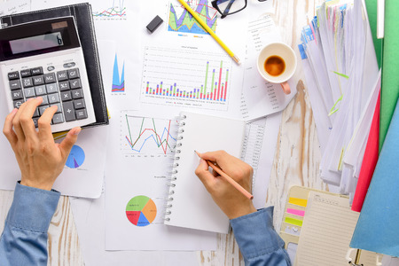 Hand on calculator on charts,graphs  accounting and pile of documents on Desk,concept for successful corporate business. Stock fotó