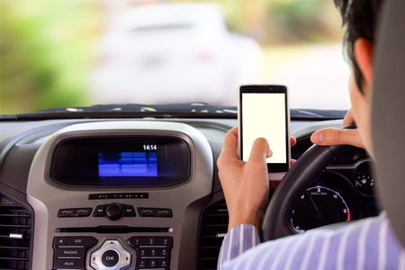 Driving while holding a mobile phone (cell phone use while driving) Stock Photo
