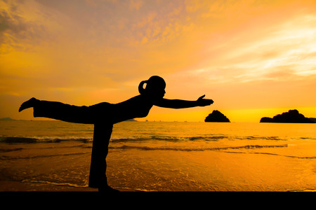 natural health: Woman making yoga on the beach at sunset time.