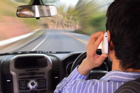 携帯電話 (運転中の携帯電話使用) を押しながら運転 写真素材