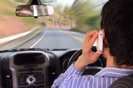 driving: Driving while holding a mobile phone (cell phone use while driving) Stock Photo