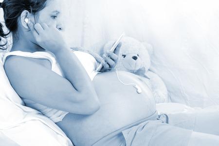 prenatal development: Pregnant women listen to music for Fetal development,Prenatal Music Stimulation baby (soft focus) Stock Photo
