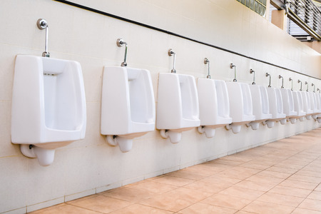 Line of white porcelain urinals in public toilets photo