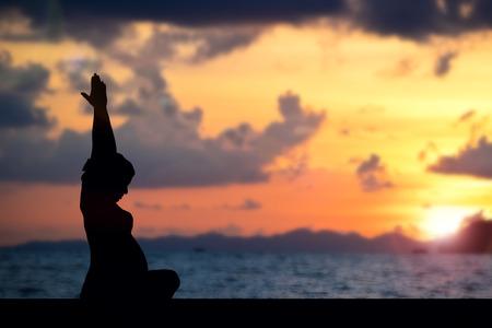 silhouette  pregnancy yoga on beach