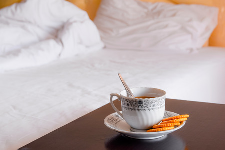 mornings: Cup of hot coffee with cookie in morning time on blurred bed