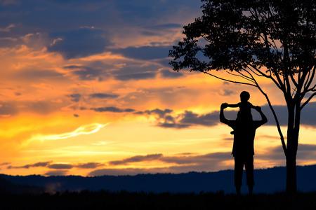 Vaderdag, vader en zoon silhouetten spelen bij zonsondergang bergen vage achtergrond