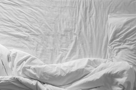 Bovenaanzicht van wit beddengoed en een kussen op ochtendtijd