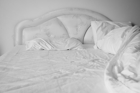 rumpled: Unmade comfortable bed is strewn with white pillows.(Shallow DOF)