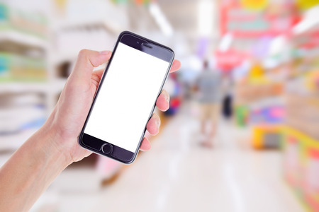 hand holding mobile smart phone on Supermarket blur background,Concept for sell shop on mobile phone