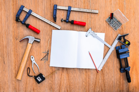 hammer and nails: Collection of worktools, set of working tools. (Steel wrench, hammer, nails, bolts, wrenches, etc.) with notebook on the wooden table.