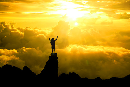 Silhouette of men backpacker open arms raised towards on hope sky at sunset light effect ,Concept for life achievements and success 免版税图像