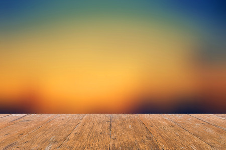 product placement: Empty old wooden table for product placement  on Abstract Sunset Blurred Background