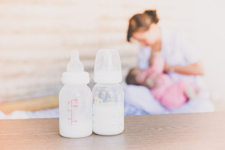 Milk storage bottle on blurred mothers breast milk is most healthy food for newborn baby