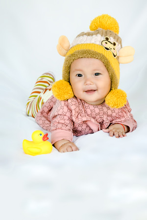 six months: Full body Six months old Asian baby girl lie leisurely on white background shallow DOF