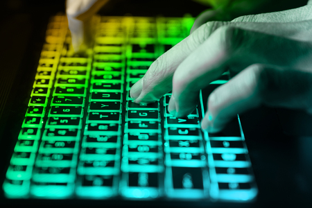 hands typing on keyboard in green light with motion blur,Concept for cybercrime hack cloud security Standard-Bild
