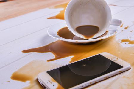 Op bureau, koffie gemorst op telefoon Stockfoto