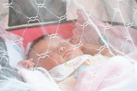 baby slaapt onder een klamboe (Shallow DOF)