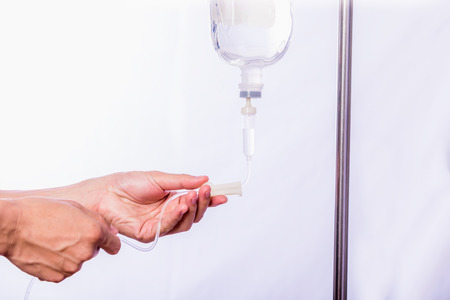 surgical oncology: Close up hand adjustment saline IV drip for patient in hospital with copy space Stock Photo
