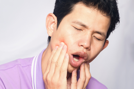 man have  toothache on white background,symptoms of toothaches typically involve some kind of ache or pain in the jaws or gums Stock Photo