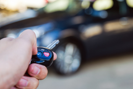 open autocar auto: Car remote control in hand man with copy space blurry car in packing background ,Shallow DOF