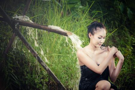 mujer ba�andose: La mujer atractiva se ba�a en cascada en el en el campo en Asia Foto de archivo