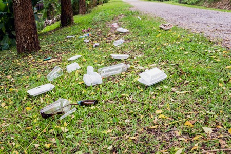 botar basura: Heap of rubbish on grass in park, plastic and glass bottles and foam box , concept for environmental protection, littering of environment Foto de archivo