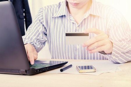 cvv: Online payment,Businessman hands holding a credit card and using with laptop concept for online shopping or e-Payment system Stock Photo