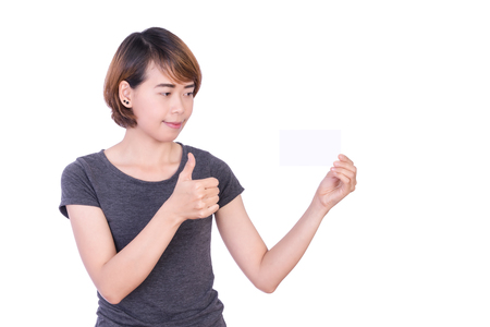 envisage: Asian People: Beautiful smart young lady showing thumbs up and look blank card paper in hand on white background Stock Photo