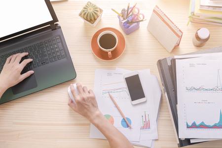 ビジネスの男性の平面図財務チャート暖かいトーン フィルターを分析するラップトップ コンピューターを使用します。
