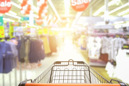 Supermarket aisle sale with empty red shopping cart with customer defocus background