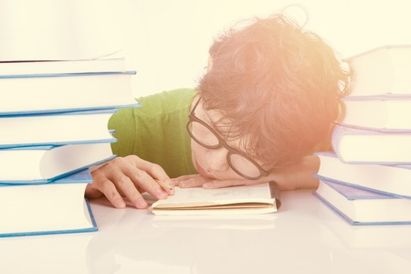 discouraged: Discouraged student sleep on table in front of his homework