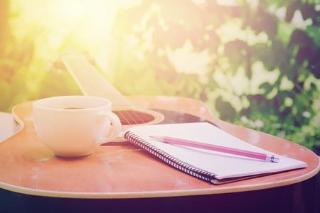 ノートブックとテーブルの上のコーヒー カップのアコースティック ギター、音楽はリラックス時間の家の庭で
