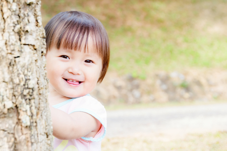 Charming asian little girl was playing happy smile in the park soft focused.