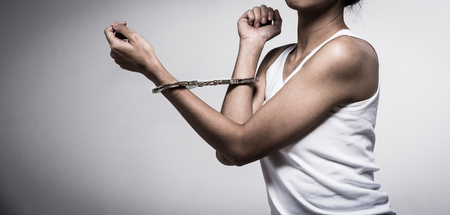 closeup young woman with handcuffs, violence or internment concept background dark tone