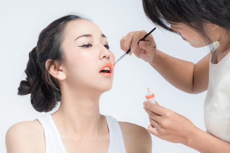 깨끗한 얼굴 패션 모델 또는 신부에게 메이크업을 적용하는 메이크업 아티스트