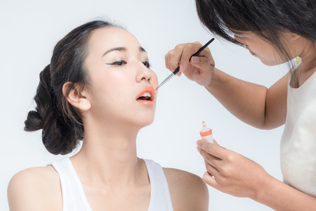 Make up artist applying make up to a clean face fashion model or bride