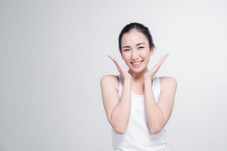 美しいアジアの幸せな若い女性が白い背景に分離されたジェスチャーだと思う姿勢で笑顔します。