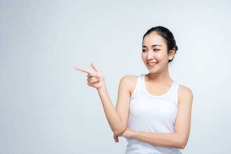 Asian young woman beautiful smile with posture point present something in blank hand isolate on white background