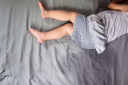 Child pee on a mattress,Little girl feet and pee in bed sheet,Child development concept ,selected focus 写真素材