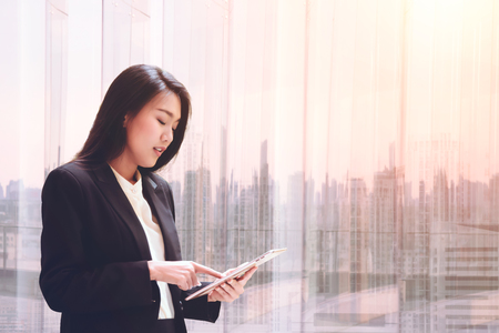 gingerish: Elegant young business woman using tablet by the window for relax, looking at screen and Business District blurred