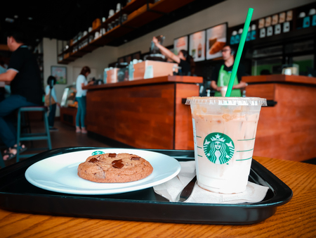 KHON KAEN ,THAILAND,17 JUNE 2017 : A Cup of Starbucks hot beverage coffee on the table in the Starbucks drive thru shop. Starbucks is the worlds largest coffeehouse company Editorial