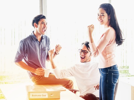 empresarios jovenes: Cheering happy business people ,Happy business team with arm raised sitting at desk in office during an office monthly meeting success, business concept background ,Activity moving blurred concept