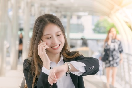 appointed: Business woman talk to smart phone andwatching wrist watch on the walk way :business concept