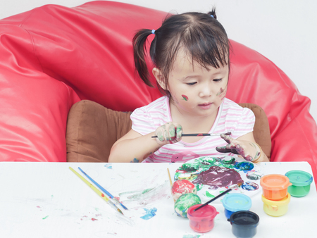 Little Girl Painting with paintbrush and colorful paints .children development concept. Stock Photo